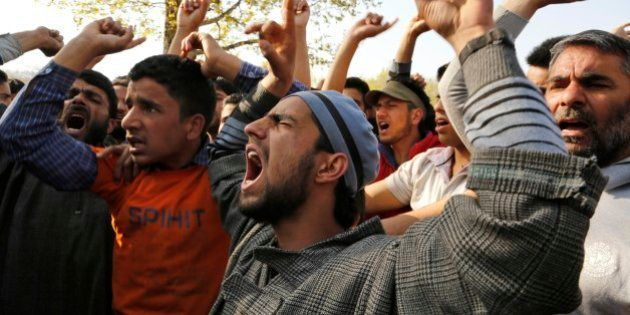 Kashmiri Muslim villagers shout slogans against Indian army during the funeral procession of Khaled Muzaffar,...