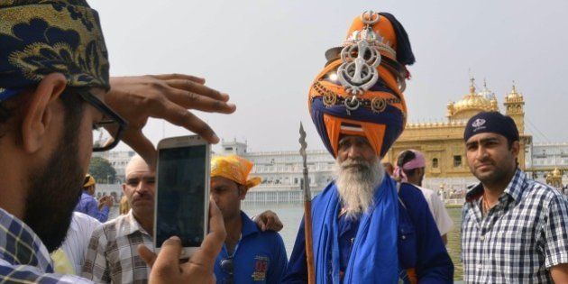 An Indian Sikh devotee (L) takes photographs of a Nihang (Sikh religious warrior) at the Sikh shrine...