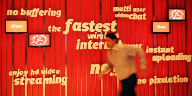 An employee of Bharti Airtel Limited runs after adjusting the screens of a promotional billboard during...