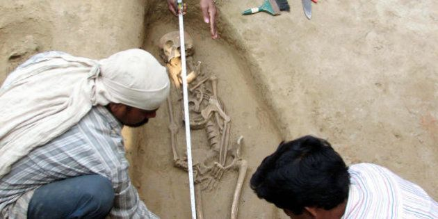Research workers of India's Vishwa Bharati University measure a human skeleton found at an excavation...