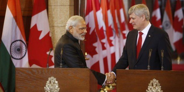 Canada's Prime Minister Stephen Harper shakes hands with India's Prime Minister Narendra Modi (L) during...