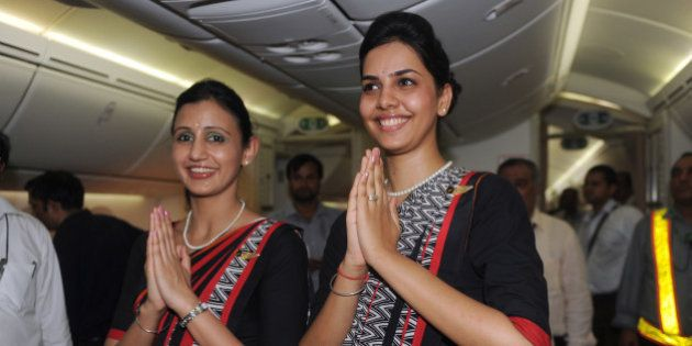 Air India flight attendants pose for a photo during the unveiling of Air India's first Boeing 787 Dreamliner...
