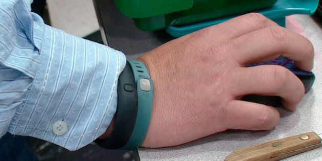 This photo from video taken Oct. 9, 2013 shows the wrist of Tim Davis wearing his FitBit, green, and...