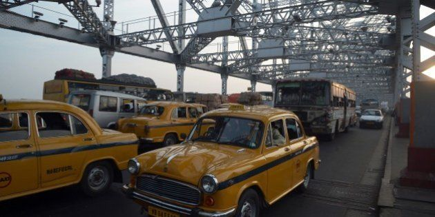 Indian commuters and taxi drivers navigate through heavy traffic on Howrah Bridge in Kolkata on November...