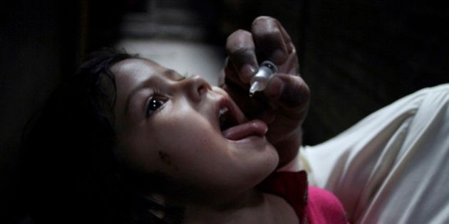 A Pakistani health worker gives polio vaccine to a child at a neighborhood of Lahore, Pakistan, Tuesday,...