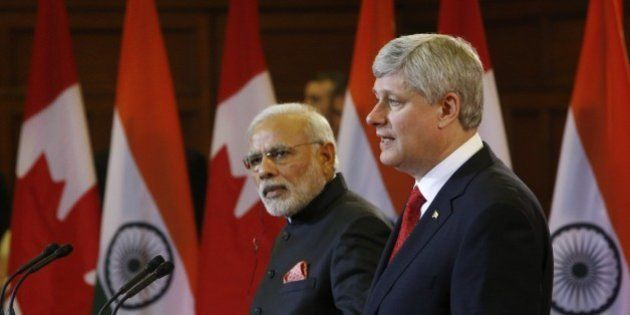 Canada's Prime Minister Stephen Harper speaks alongside India's Prime Minister Narendra Modi (L) during...