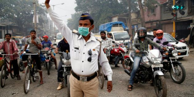 A traffic policeman wears a mask and controls traffic on a busy road in Mumbai, India, Tuesday, April...