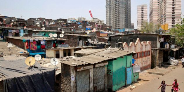 Indian girls of a shanty town cycle near apartment buildings under construction in Mumbai, India, Thursday,...