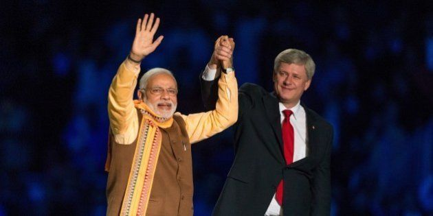 Canadian Prime Minister Stephen Harper (R) and Indian Prime Minister Narendra Modi (L) acknowledge the...