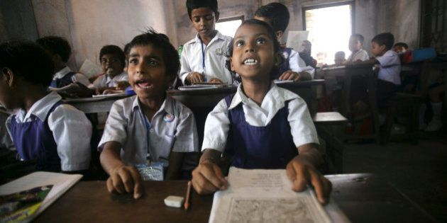 Indian students take lessons from their teacher inside a classroom at a school in Calcutta, India, Thursday,...