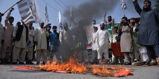 Pakistani activists from the banned organisation Jamaat-ud-Dawa (JuD) shout slogans beside a burning...