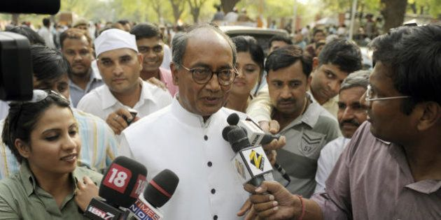 Congress Party General Secretary Digvijay Singh is surrounded by journalists as he exits Congress Party...