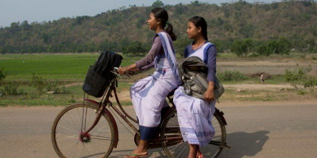 Indian girls go to a school on a bicycle at Roja Mayong village about 40 kilometers (25 miles) east of...
