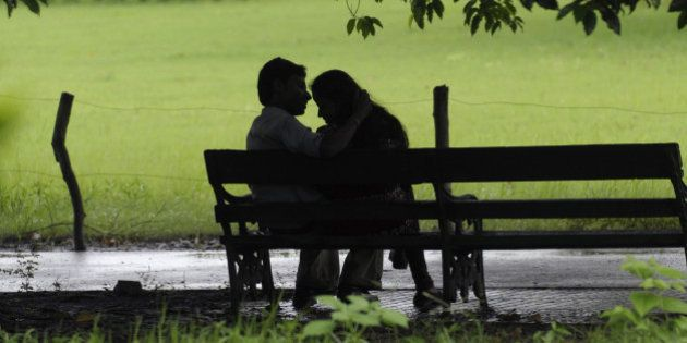An Indian couple sit on a bench near the Victoria Memorial complex on Friendship Day in Kolkata on August...