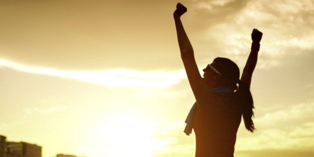 Happy successful sportswoman raising arms to the sky on golden back lighting sunset summer. Fitness athlete...