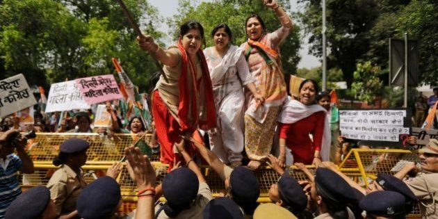 Activists of India's opposition Congress party's women's wing climb police barricades and shout...