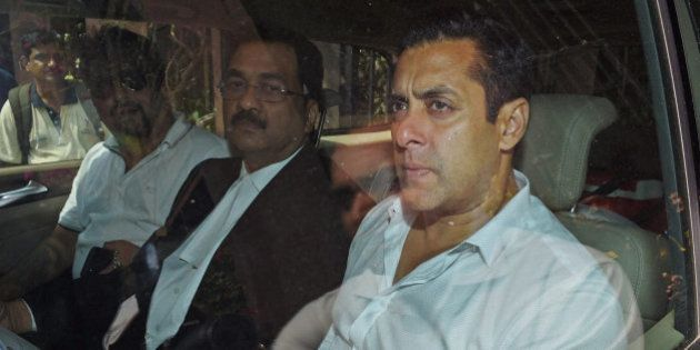 Bollywood actor Salman Khan, right, sits in a car outside a court in Mumbai, India, Friday, March 27,...