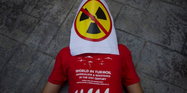 A protestor lies on the ground with an anti-nuclear placard covering his face during a protest in Bangi...