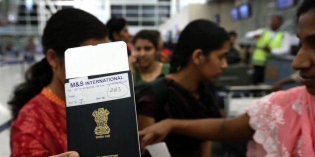 An Indian nurse holds up her passport as she and other Indian nurses, held hostage by Islamic militants...