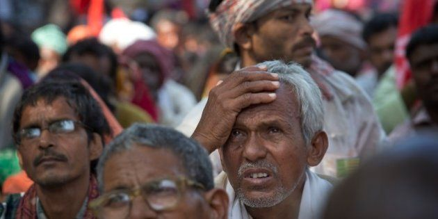 An Indian farmer listens to a speaker as they gather near the parliament for a protest against the land...