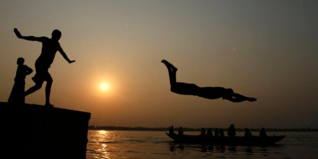An Indian boy dives into the River Ganges, as tourists ride a boat in Varanasi, India, Thursday, Sept....