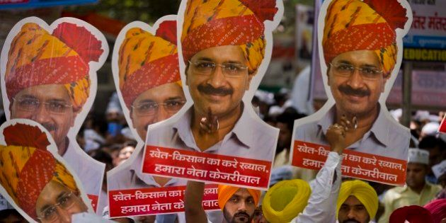 Indian farmers and Aam Aadmi Party or Common man's party supporters display pictures of Delhi Chief...