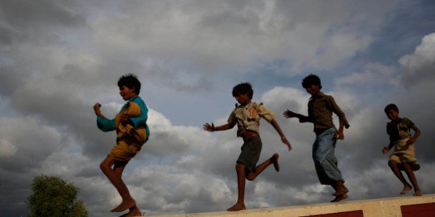 Children play as monsoon clouds hover in the sky, in Allahabad, India, Sunday, July 6, 2014. The monsoon...