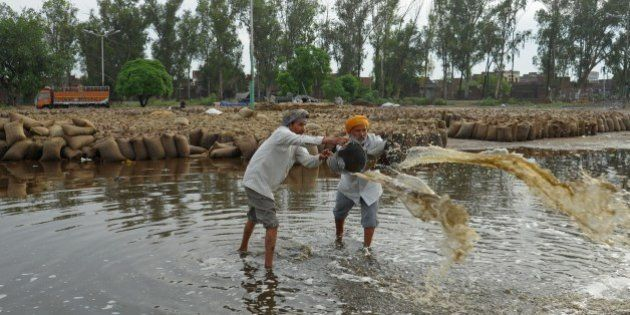Indian labourers bail accumulated rainwater near flooded sacks of wheat after unseasonal overnight rains...
