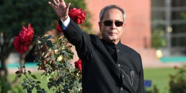 Indian President Pranab Mukherjee gestures to media during a photocall at The Mughal Garden at the Presidential...