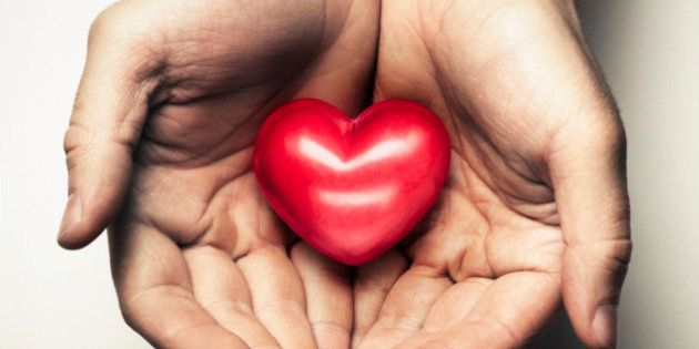 Two hands cup a heart in a caring and loving way. The heart symbolises love and