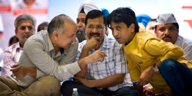 Delhi Chief Minister Arvind Kejriwal sits flanked by Aam Aadmi Party or Common man's party leaders...
