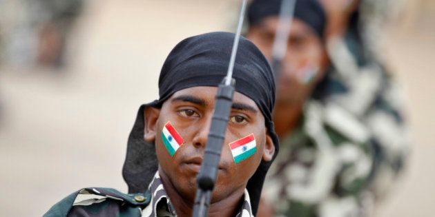 An Indian Central Reserve Police Force (CRPF) personnel with national flag painted on his face participates...
