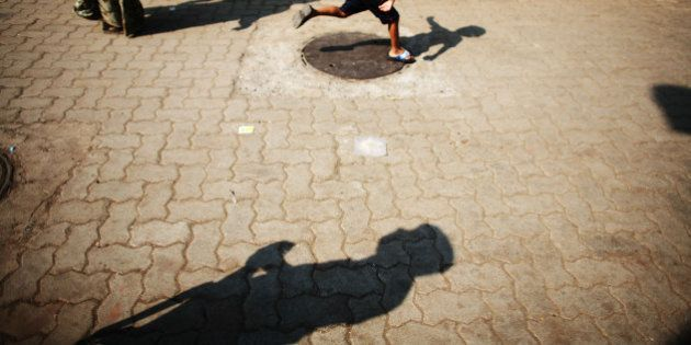 MUMBAI (BOMBAY), INDIA - DECEMBER 03: (ISRAEL OUT) A policeman's silhouette is cast on the ground as...
