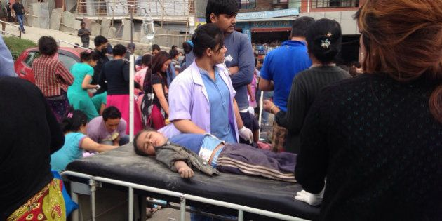 An injured child receives treatment outside Medicare Hospital in Kathmandu, Nepal, Saturday, April 25,...