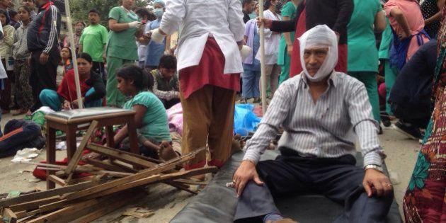 Injured people receive treatment outside the Medicare Hospital in Kathmandu, Nepal, Saturday, April 25,...