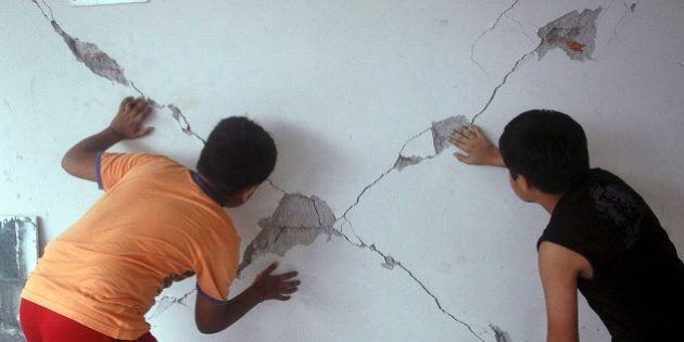 Young Indian children look at a crack caused by Sunday's earthquake in Siliguri, India, Monday, Sept....