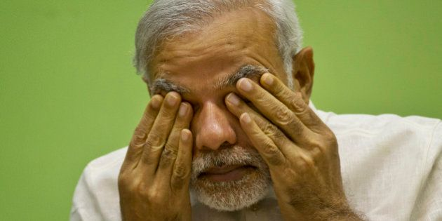 India's Prime Minister Narendra Modi rubs his eye as he attends a conference by The Environment Ministry...