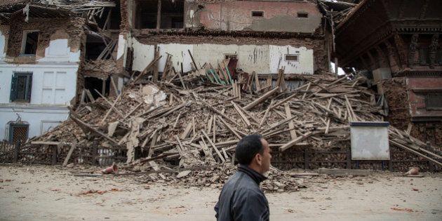KATHMANDU, NEPAL - APRIL 25: A Kathmandu resident passes in front of a collapsed temple at Basantapur...