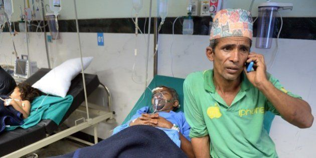A Nepalese resident talks on the phone as his relative Megh Nath (2R), is treated for injuries sustained...