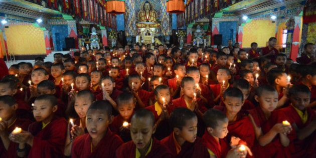 Novice Buddhist monks light candles and offer prayers for victims of Nepal's earthquake, in Bodhgaya,...