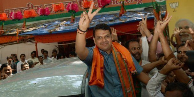 Indian Bharatiya Janata Party (BJP)'s Maharashtra state unit president Devendra Fadnavis flashes the...