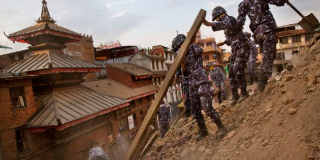 Nepalese policemen clear the debris at Basantapur Durbar Square, damaged in Saturday's earthquake,...