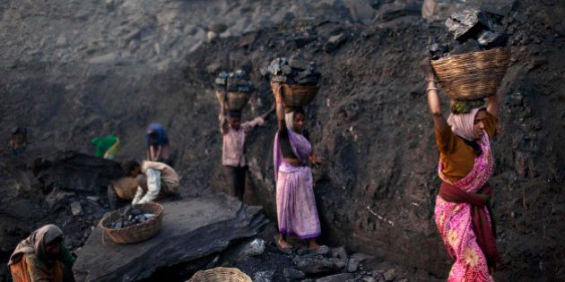 FILE - In this Jan. 7, 2011 file photo, people carry baskets of coal scavenged illegally at an open-cast...