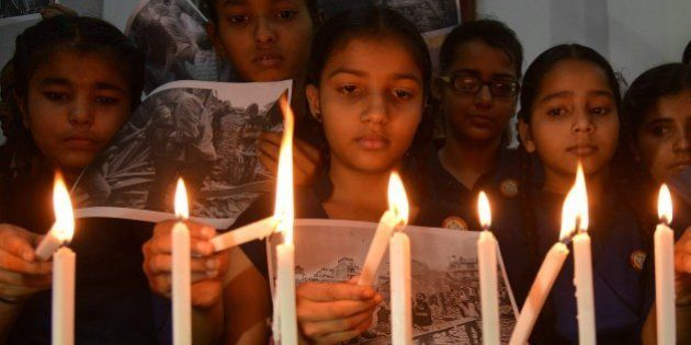 Indian schoolgirls light candles for the victims of an earthquake in Nepal at a school in Amritsar on...