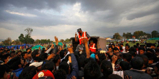A Nepalese policeman requests earthquake victims to stand in a queue to receive tents in Kathmandu, Nepal,...