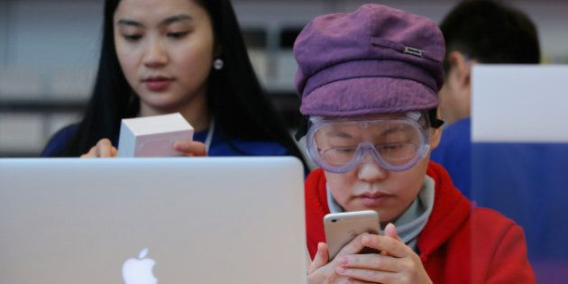 BEIJING, CHINA - OCTOBER 17: A Chinese woman sets up her new iPhone 6 with the help of an Apple store...