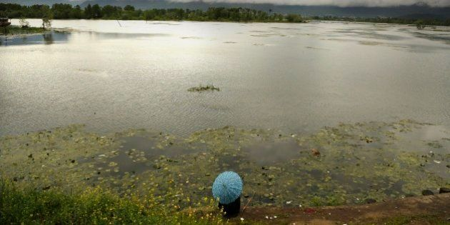 A Kashmiri man holds an umbrella as he fishes sitting on the banks of the Nigeen Lake on a rainy day...