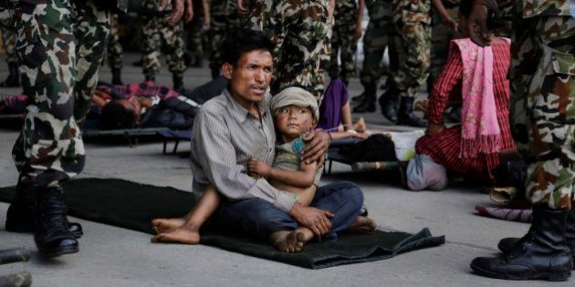 A man sits with a child on his lap as victims of Saturday's earthquake, wait for ambulances after being...