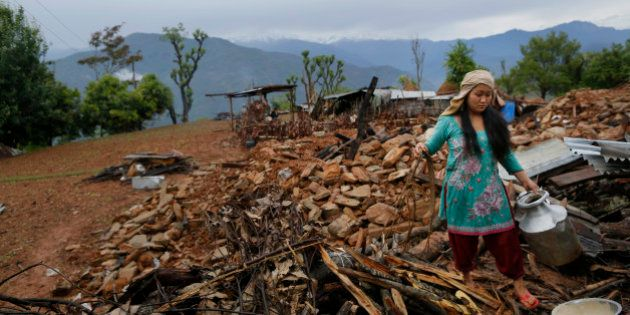 A woman recovers cooking pots from her collapsed home destroyed village of Paslang near the epicenter...