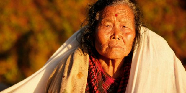 An elderly villager sit in the evening sun with a blanket in the destroyed village of Paslang near the...